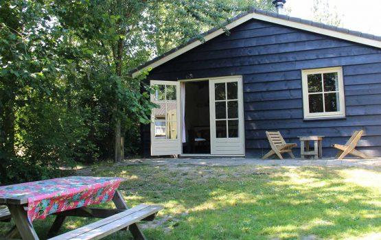 Groene_Camping_In_de_polder_Polderhuisje_buiten_aan_tafel