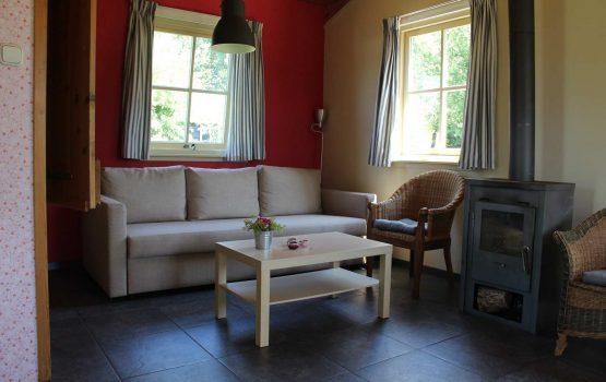 Groene_Camping_In_de_polder_Polderhuisje_gezellige-kamer-met-houtkachel